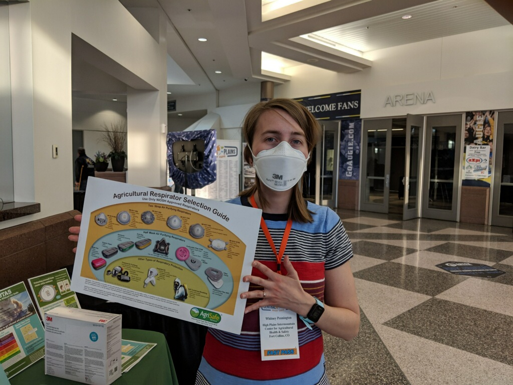 Woman wears a respirator while holding a sign about choosing a respirator