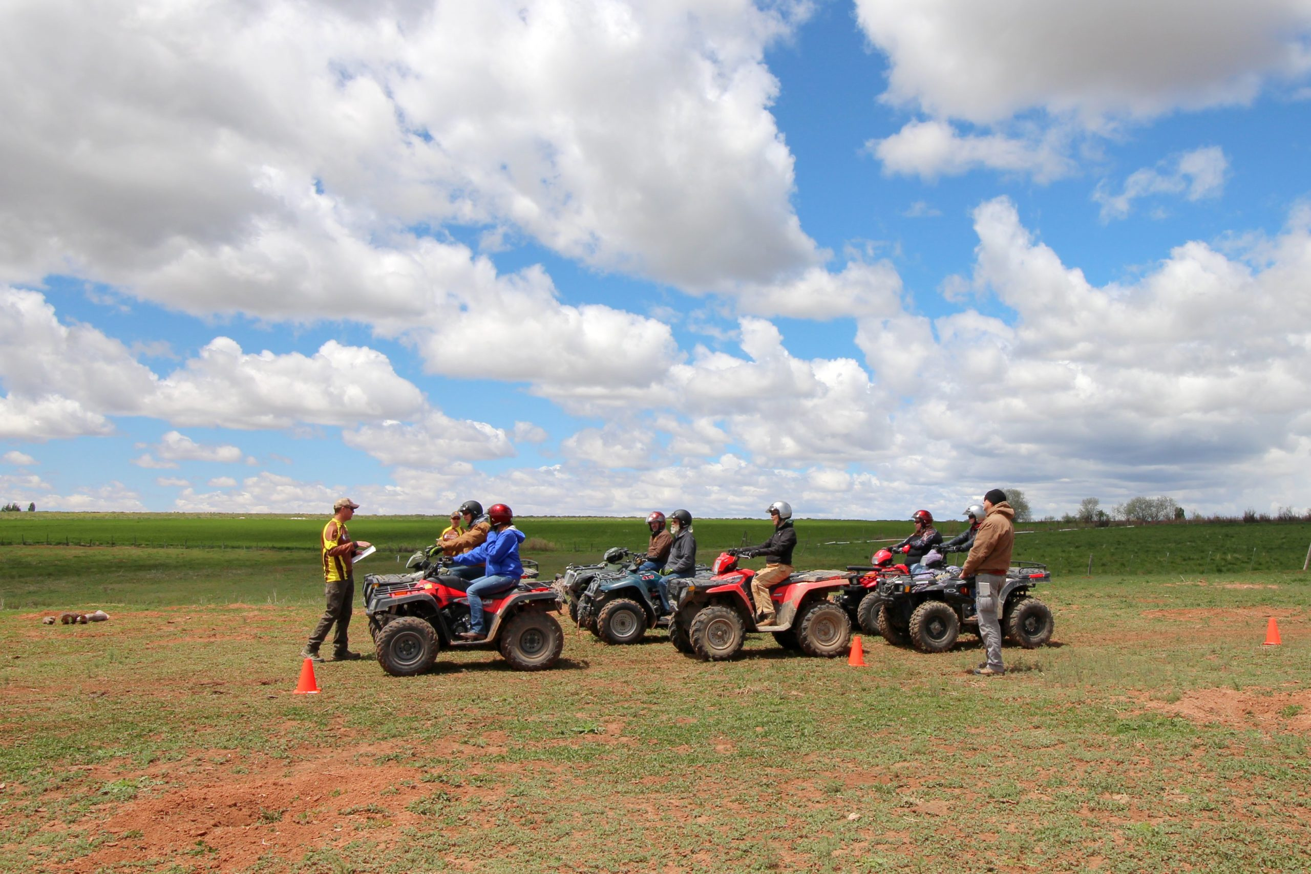 A man instructing six people on parked ATVs in a field